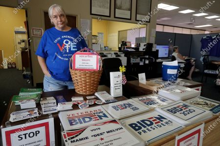 Chris Stanley, leader of The Villages Democrats Club, shows off some of the signs available at the Democratic Headquarters, in Wildwood, Fla. Residents of The Villages say they've never seen anything like the politically inspired hostilities that have surfaced over the past several months