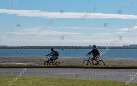 Two cyclists enjoy a sunny day on the Bayside amid Covid-19 crisis. Queensland Premier Annastacia Palaszczuk takes part of a state's cabinet meeting on Tuesday 30 June to announce possible border reopening and health recommendations.