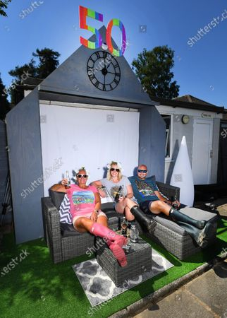 Coronavirus Crisis Fans Recreate Cancelled Festival in Their Gardens. If you can't go to Glastonbury... bring Glastonbury to you! Festival fans who'd hoped to spend this weekend watching Sir Paul McCartney or Taylor Swift have had their plans scuppered by coronavirus. But rather than let any glorious weather go to waste, ticket-holders across the country have decided to recreate the Somerset extravaganza in their own gardens - and share the results on social media under the hashtag #Glasthomebury.Glastonbury 2020- Sittig in their tent, Fiona Rees,50,(pink wellies) with her neighbours Emma Martin,38,(grey top) and Wayne Freer,40, and Labrador Dexter, from Droitwich, Worcs., who are celebrating the 50th Annv. of Glastonbury Festival at home remotely due to the Coronavirus crisis.