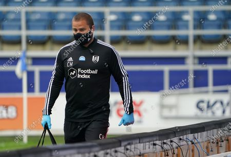The Fulham physio wearing gloves and a protective mask walks around the pitch