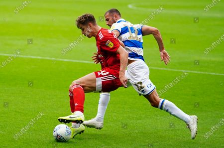 Tom Cairney of Fulham battles with Dominic Ball of QPR