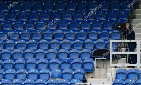 A television cameraman films in an empty stadium