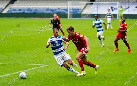 Tom Cairney of Fulham looks to get past Dominic Ball of QPR