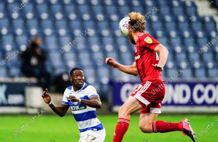 Tim Ream of Fulham heads clear as Olamide Shodipo of QPR looks on