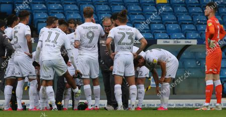 Leeds manager Marcelo Bielsa taks to his players on a water break