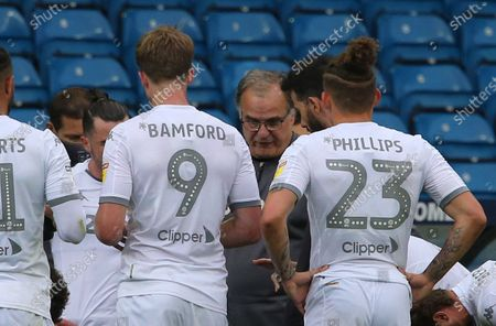 Leeds manager Marcelo Bielsa talks to his players on a water break