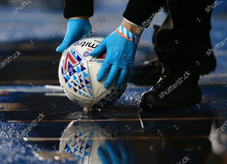 The EFL Mitre match ball is held with rubber gloves