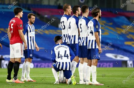 Aaron Connolly of Brighton & Hove Albion kneels behind the wall for a free kick.