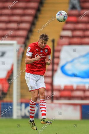 Mads Andersen (6) of Barnsley heads the ball back up field
