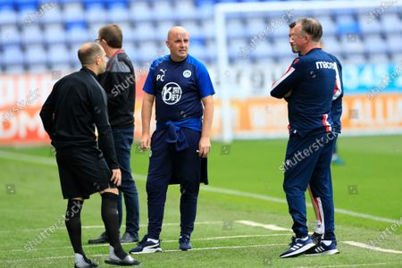 Wigan Althletic manager Paul Cook and Stoke City manager Michael O'Neill chat on the sidelines before the game