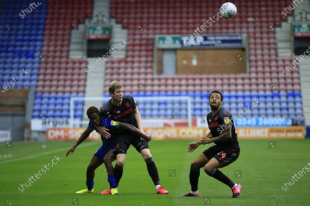 Nathan Collins (37) of Stoke City challenges Jamal Lowe (9) of Wigan Athletic with Jordan Cousins (24) of Stoke City watching on