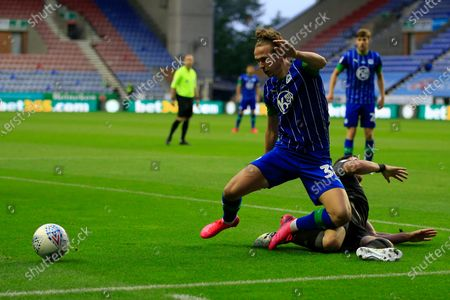 Kai Naismith (33) of Wigan Athletic is challenged by Stephen Ward (3) of Stoke City