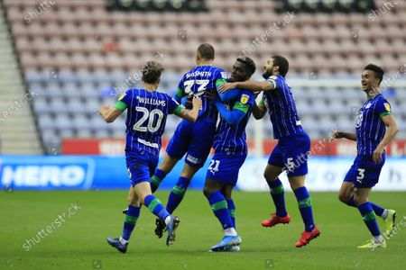 Wigan players congratulate Kai Naismith (33) after scoring his teams third goal with a long range shot in the 68th minute, 3-0 Wigan