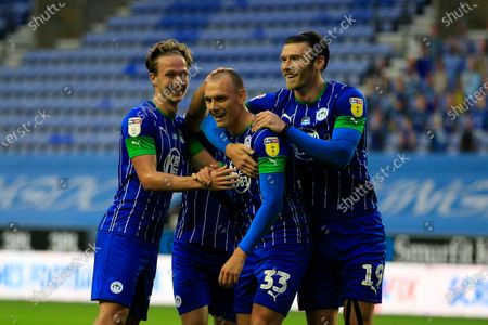 Wigan players congratulate Kai Naismith (33) after scoring his teams second goal in the 65th minute, 2-0 Wigan