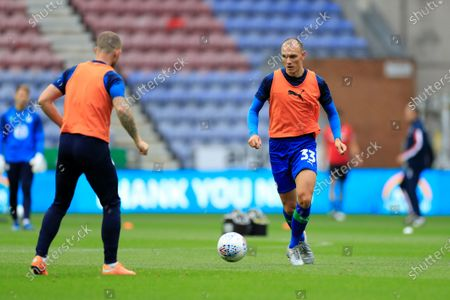 Kai Naismith (33) of Wigan Athletic warms up for the game