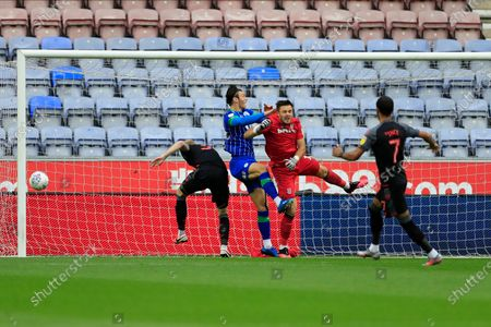Jack Butland (1) of Stoke City gets hurt in a duel with Kieffer Moore (19) of Wigan Athletic