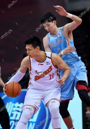 Zhou Qi (R) of Xinjiang Flying Tigers blocks Xu Zhonghao of Bayi Rockets during a match between Bayi Rockets and Xinjiang Flying Tigers at the 2019-2020 Chinese Basketball Association (CBA) league in Qingdao, east China's Shandong Province, June 30, 2020.