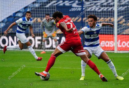 Cyrus Christie of Fulham plays the ball around Luke Amos of QPR