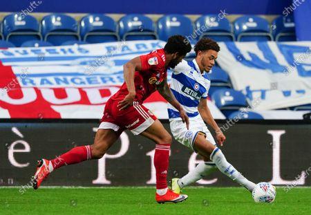Luke Amos of QPR plays the ball around Cyrus Christie of Fulham