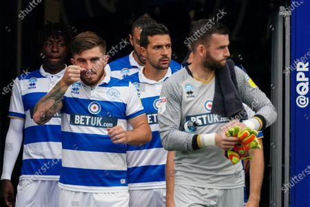 Yoann Barbet of QPR (centre) and the starting QPR team walk out on to the pitch