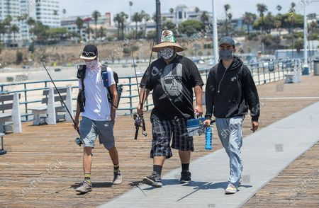 Left to right-Friends Adrian Sanchez, 20, Matthew Gonzalez, 22, and Justice Arreola, arrive at the Santa Monica Pier in Santa Monica to do some fishing. They are all from Santa Monica. L.A. County is expected to reach 100,000 cases of coronavirus. (Mel Melcon / Los Angeles Times)