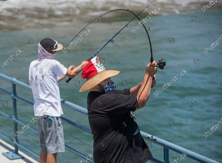 Stock Picture of Adrian Sanchez, 20, left, and friend Matthew Gonzalez, 22, wear protective face covering to protect against the coronavirus while fishing off of the Santa Monica Pier in Santa Monica on June 29, 2020. They are both from Santa Monica. L.A. County is expected to reach 100,000 cases of coronavirus. (Mel Melcon / Los Angeles Times)