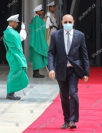 Mauritanian President Mohamed Ould Ghazouani (R) wears a face mask as he walks past a guard of honor to welcome the French president upon his arrival at Nouakchott-Oumtounsy International Airport, in Nouakchott, Mauritania, 30 June 2020, to attend a G5 Sahel summit. The leaders of the G5 Sahel West African countries and their ally France are meeting to confer over their troubled efforts to stem a jihadist offensive unfolding in the region, six months after rebooting their campaign in Pau, southwestern France.