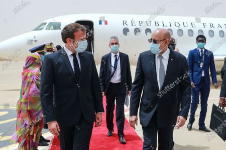 French President Emmanuel Macron (L) is welcomed by Mauritanian President Mohamed Ould Ghazouani (R) upon arrival at Nouakchott-Oumtounsy International Airport, in Nouakchott, Mauritania, 30 June 2020, to attend a G5 Sahel summit. The leaders of the G5 Sahel West African countries and their ally France are meeting to confer over their troubled efforts to stem a jihadist offensive unfolding in the region, six months after rebooting their campaign in Pau, southwestern France.