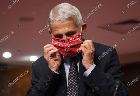 Dr. Anthony Fauci, director of the National Institute for Allergy and Infectious Diseasesdjusts his face mask as he prepares to testify before the Senate Health, Education, Labor and Pensions (HELP) Committee on Capitol Hill in Washington DC. Fauci and other government health officials updated the Senate on how to safely get back to school and the workplace during the COVID-19 pandemic.