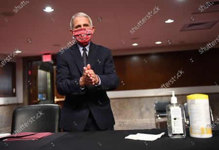 Dr. Anthony Fauci, director of the National Institute for Allergy and Infectious Diseases, cleans his hands as he prepares to testify before the Senate Health, Education, Labor and Pensions (HELP) Committee on Capitol Hill in Washington DC. Fauci and other government health officials updated the Senate on how to safely get back to school and the workplace during the COVID-19 pandemic.
