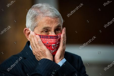 Anthony Fauci, director of the National Institute of Allergy and Infectious Diseasesdjusts a Washington Nationals protective mask while arriving to a Senate Health, Education, Labor and Pensions Committee hearing in Washington, D.C., U.S.,. Top federal health officials are expected to discuss efforts to get back to work and school during the coronavirus pandemic.