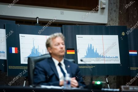 Charts of coronavirus data from France and Germany are seen as United States Senator Rand Paul (Republican of Kentucky), listens during a Senate Health, Education, Labor and Pensions Committee hearing in Washington, D.C., U.S.,. Top federal health officials are expected to discuss efforts to get back to work and school during the coronavirus pandemic.