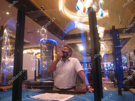 Joe Lupo, president of the Hard Rock casino in Atlantic City N.J. examines the installation of protective barriers being installed at a card table on the casino floor. Smoking, drinking and eating will all be prohibited when Atlantic City's casinos reopen after being shut for three months due to the coronavirus outbreak under rules imposed by New Jersey Gov. Phil Murphy on June 29, 2020