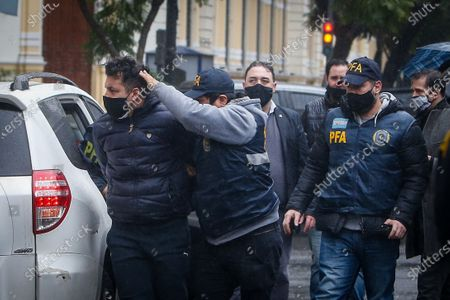 Members of the police guard the transfer of Facundo Melo accused in the espionage case involving former President Mauricio Macri in Buenos Aires, Argentina 30 June 2020. The Argentine Federal Justice arrested on Tuesday two former officials of the Government of former President Mauricio Macri (2015-2019) and 20 other people suspected of alleged illegal espionage of officials, politicians, trade unionists and businessmen, official sources reported.
