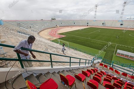 Man runs cables prior to the reopening of the soccer stadium in Mogadishu, Somalia . At least three mortar blasts struck the Mogadishu Stadium Tuesday evening, just hours after it was reopened by Somalia's President Mohamed Abdullahi Mohamed, who had left before the shells hit, following years of instability