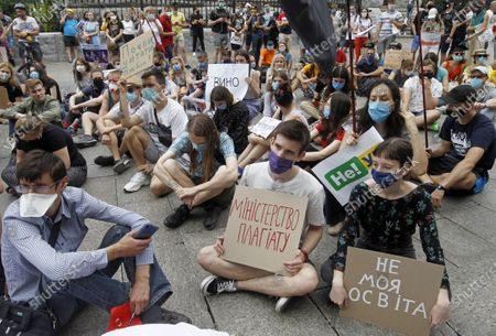 Students sit down while displaying placards outside the Presidential Administration in Kiev. Students and scientists held their sedentary protest against the newly appointed acting Minister of Education and Science Serhiy Shkarlet demanding his resignation because he was a member of the Party of Regions and supported former president Viktor Yanukovych, reported by media.