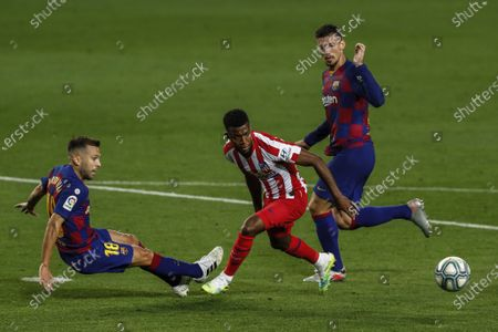 Atletico Madrid's Thomas Lemar, center, views for the ball next to Barcelona's Jordi Alba, left, and Barcelona's Clement Lenglet, right, during the Spanish La Liga soccer match between FC Barcelona and Atletico Madrid at the Camp Nou stadium in Barcelona, Spain