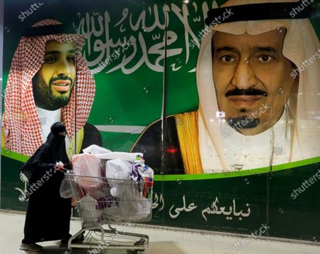 """Saudi woman pushes her shopping cart outside a supermarket a day before the expected increase of VAT from 5% to 15%, in Jiddah, Saudi Arabia, . At background a banner showing Saudi King Salman, right, and his Crown Prince Mohammed bin Salman with Arabic reads, """"We pledge you to love and loyalty"""