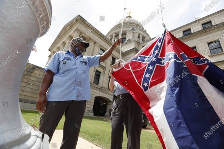Mississippi Department of Finance and Administration employees Willie Townsend, left, and Joe Brown, attach a Mississippi state flag to the harness before raising it over the Capitol grounds in Jackson, Miss., . The two men raised about 100 flags, provided by the Secretary of State's office, for people or organizations that purchased a state flag that flew over the grounds. Gov. Tate Reeves will sign a bill Tuesday evening retiring the last state flag with the Confederate battle emblem during a ceremony at the Governor's Mansion. Upon the governor signing the bill, the flag will lose its official status