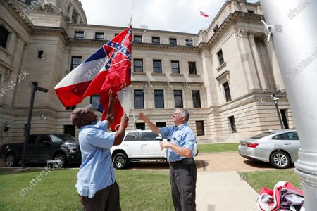 Mississippi Department of Finance and Administration employees Willie Townsend, left, and Joe Brown, raise a couple of Mississippi state flags over the Capitol grounds in Jackson, Miss., . The two men raised and lowered about 100 flags, provided by the Secretary of State's office, for people or organizations that purchased a state flag that flew over the grounds. Gov. Tate Reeves will sign a bill Tuesday evening retiring the last state flag with the Confederate battle emblem during a ceremony at the Governor's Mansion. Upon the governor signing the bill, the flag will lose its official status