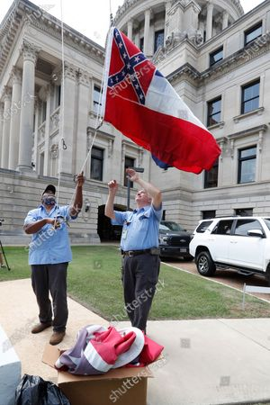 Mississippi Department of Finance and Administration employees Willie Townsend, left, and Joe Brown, raise a couple of Mississippi state flags over the Capitol grounds in Jackson, Miss., . The two men raised and lowered about 100 flags, provided by the Secretary of State's office, for people or organizations that purchased a state flag that flew over the grounds. Gov. Tate Reeves will sign a bill that evening retiring the last state flag with the Confederate battle emblem during a ceremony at the Governor's Mansion. Upon the governor signing the bill, the flag will lose its official status