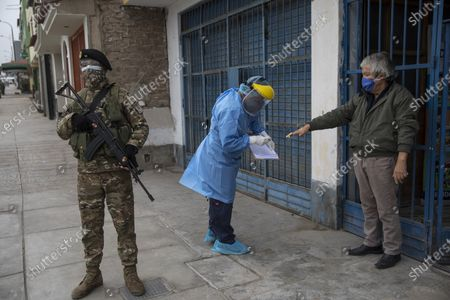 Escorted by a soldier, Doctor Jose Pimentel attends Petroni Gutierrez Rivera, 68, during a house-to-house coronavirus testing drive in Villa el Salvador, on the outskirts of Lima, Peru