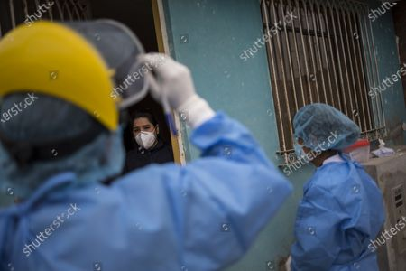 Stock Photo of Giseli del Pilar, 29, listens to Doctor Jose Pimentel during a house-to-house coronavirus testing drive in Villa el Salvador, on the outskirts of Lima, Peru