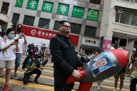North Korean leader Kim Jong-un impersonator, who goes by the name Howard X, pose for photos holding a balloon rocket with Chinese President Xi Jinping picture on it during a rally against a new national security law in Causeway Bay on the 23rd anniversary of the establishment of the Hong Kong Special Administrative Region in Hong Kong, China, 01 July 2020. Chinese President Xi Jinping has signed into law the national security legislation Beijing has tailor-made for Hong Kong, prohibiting acts of secession, subversion, terrorism and collusion with foreign forces to endanger national security.