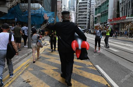 North Korean leader Kim Jong-un impersonator, who goes by the name Howard X, waves as he walks holding a balloon rocket with Chinese President Xi Jinping picture on it during a rally against a new national security law on the 23rd anniversary of the establishment of the Hong Kong Special Administrative Region in Hong Kong, China, 01 July 2020. The new national security law, that Beijing has tailor-made for Hong Kong, prohibits acts of secession, subversion, terrorism and collusion with foreign forces to endanger national security.