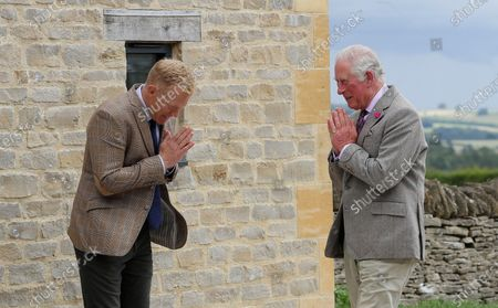 Britain's Prince Charles, right, is greeted by farmer and television personality Adam Henson during a visit to Cotswold Farm Park in Guiting Power near Cheltenham, England, . The visit to Cotswold Farm Park highlights the important work that these farm parks do in preserving British native breeds, encouraging visitors to return to them when they re-open and go back regularly throughout the year to watch the animals change and grow