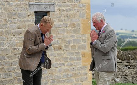 Britain's Prince Charles, right, is greeted by farmer and television personality Adam Henson during a visit to Cotswold Farm Park in Guiting Power near Cheltenham, England, Wednesday, July 1, 2020. The visit to Cotswold Farm Park highlights the important work that these farm parks do in preserving British native breeds, encouraging visitors to return to them when they re-open and go back regularly throughout the year to watch the animals change and grow.