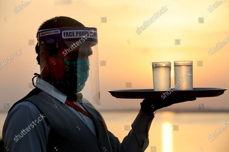 A waiter, wearing a face shield carries glasses of water in a restaurant as the sun sets in the background in Bhopal, India, 01 July 2020. Countries around the world are taking measures to stem the spread of the SARS-CoV-2 coronavirus, which causes the COVID-19 disease
