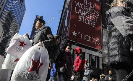 """A shopper leaves Macy's department store with bags in both hands during Black Friday shopping in New York. Macy's is refashioning what the Black Friday sales bonanza will look like in a pandemic. The company's CEO Jeff Gennette told analysts, said that the department store chain will be pivoting its Black Friday business more toward online and will likely be going """"full force"""" with marketing right after Halloween"""
