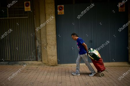 Luis Miguel Beaumont, 57 years old unemployed pulls his trolley along a street to his home after received from charity foundation Caritas a pack of foods for the next two weeks, in Estella, around 38 kms (23, 61 miles) from Pamplona, northern Spain, . Spain is beginning to suffer an economic crisis due to the coronavirus pandemic